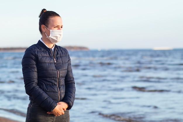 Triste infeliz menina frustrada pensativa, jovem chateado mulher desesperada em máscara protetora médica no rosto contra coronavírus andando no mar da praia. vírus, depressão, isolamento, epidemia, conceito de drama