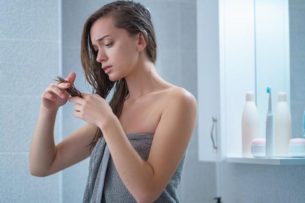 Triste infeliz morena jovem numa toalha de banho com cabelos longos, olhando para a divisão danificada termina no banheiro após o banho em casa. problemas capilares e tratamento de pontas duplas