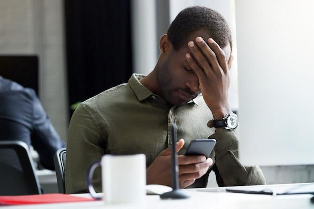 Triste jovem africano lendo a mensagem em seu telefone móvel