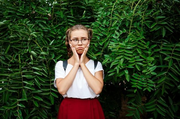 Triste jovem aluna bonita em copos posando sobre folhas ao ar livre.