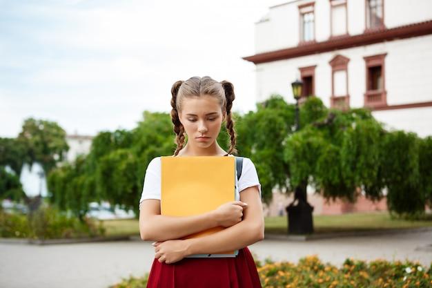 Triste jovem bela aluna olhando para baixo segurando pastas ao ar livre