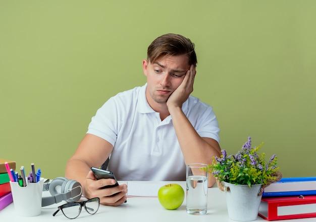 Triste jovem bonito estudante do sexo masculino sentado na mesa com as ferramentas da escola segurando e olhando para o telefone isolado em verde oliva