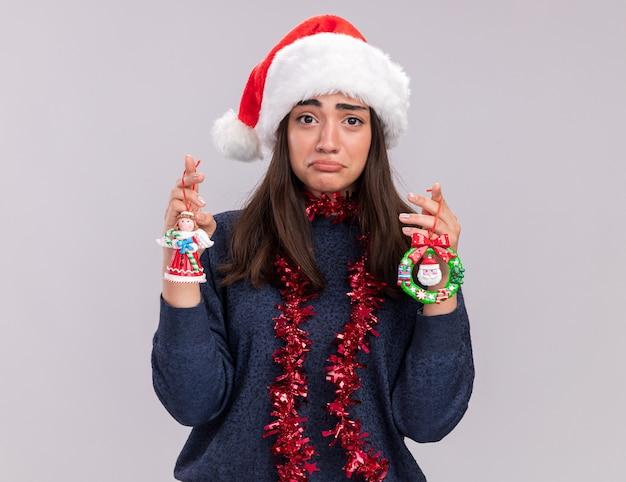 Triste jovem caucasiana com chapéu de papai noel e guirlanda no pescoço segurando brinquedos da árvore de natal