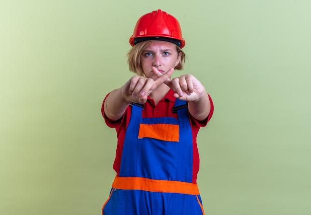 Triste jovem construtora de uniforme mostrando gesto de não isolado na parede verde oliva