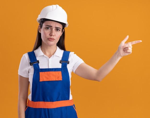 Triste jovem construtora uniformizada apontando para o lado isolado na parede laranja