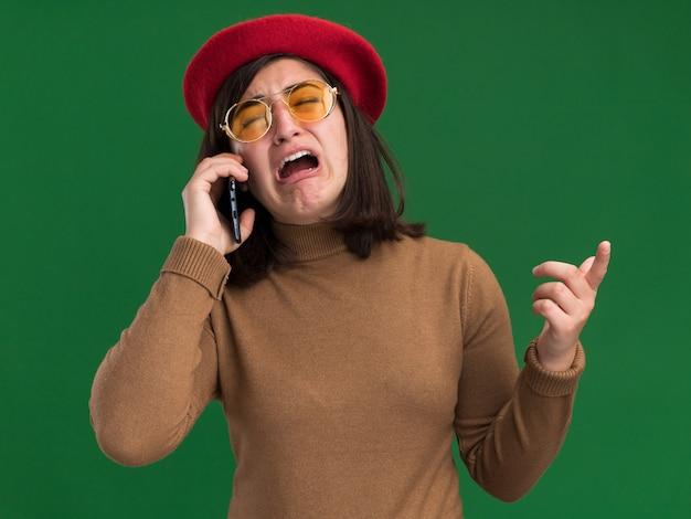 Triste jovem e bonita caucasiana com chapéu de boina e óculos de sol falando no telefone, isolada em uma parede verde com espaço de cópia