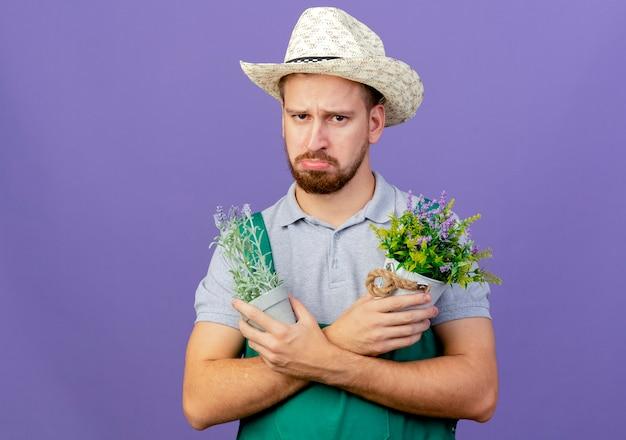 Triste jovem e bonito jardineiro eslavo de uniforme e chapéu olhando, de mãos cruzadas, segurando vasos de flores isolados