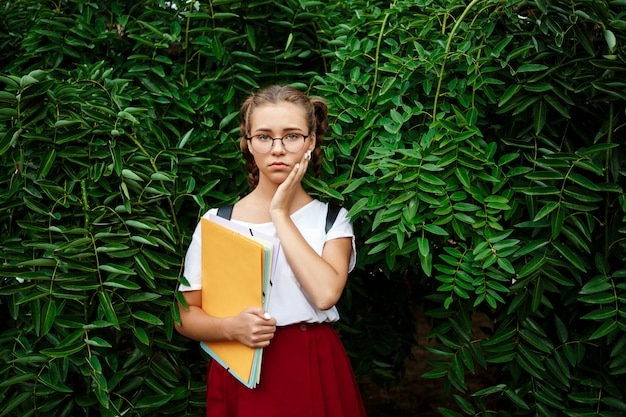 Triste jovem estudante feminino bonita de óculos, segurando pastas ao ar livre.