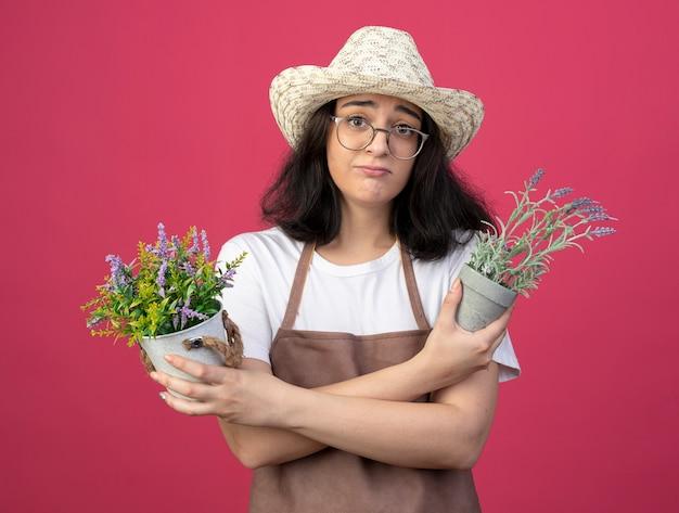 Triste jovem morena jardineira feminina de óculos ópticos e uniforme, usando chapéu de jardinagem, segurando vasos de flores isolados na parede rosa com espaço de cópia