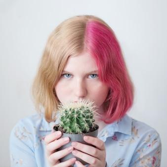 Triste menina adolescente segurando o cacto no vaso de flores