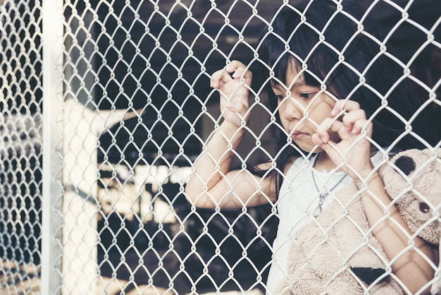 Triste menina asiática criança sozinha em gaiola foi preso não fazer liberdade ou falta de liberdade