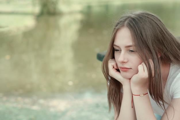 Triste menina jovem, adolescente. feche o retrato de mulher meditando. cena ao ar livre. copie o espaço.