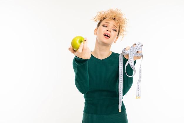 Triste menina loira encaracolada detém uma fita métrica e uma maçã verde nas mãos em branco
