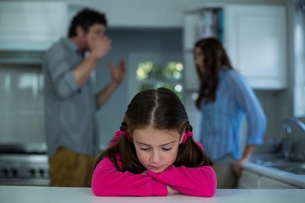 Triste menina sentada enquanto casal tendo argumento