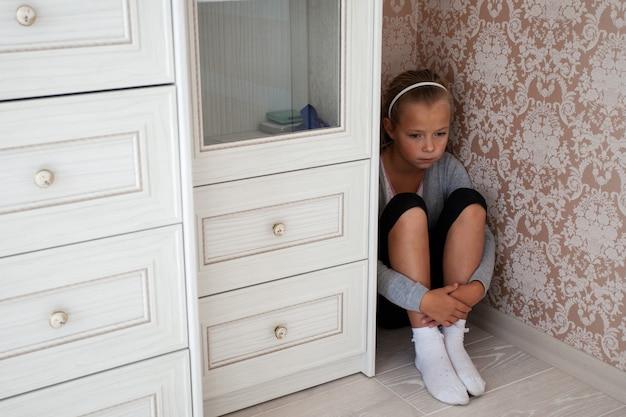 Triste menina sentada no canto de uma sala