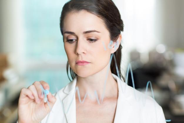 Triste mulher de negócios bonita graph drawing on glass
