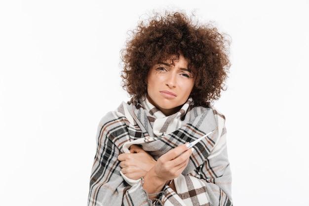 Triste mulher doente em pé envolto em um cobertor