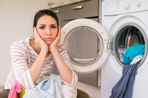Triste mulher fazendo retrato de lavanderia