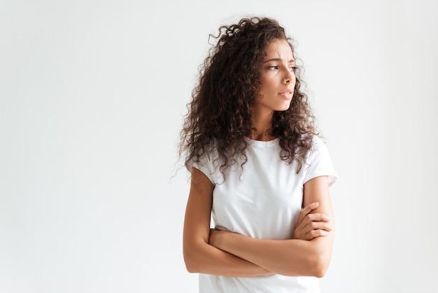 Triste mulher jovem com cabelos cacheados em pé com os braços cruzados