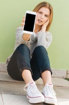 Triste, mulher jovem, sentando, contra, a, parede verde, mostrando, telefone móvel