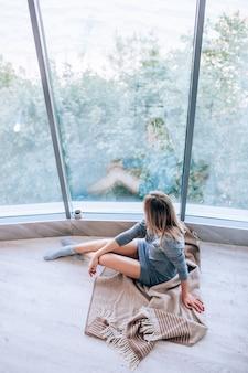 Triste mulher magra, sentada num chão quente perto da grande janela