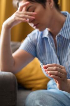 Triste mulher segurando a aliança de casamento