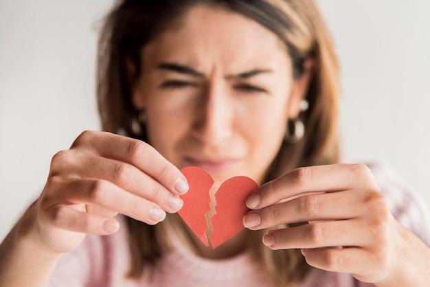 Triste mulher segurando coração partido