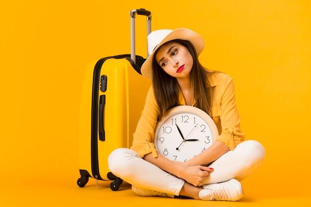 Triste mulher segurando o relógio e posando ao lado de bagagem