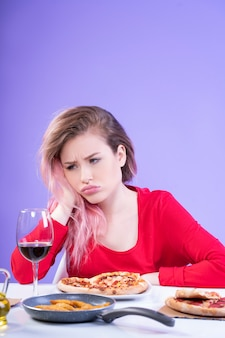 Triste mulher sentada à mesa com um copo de vinho tinto e pizza