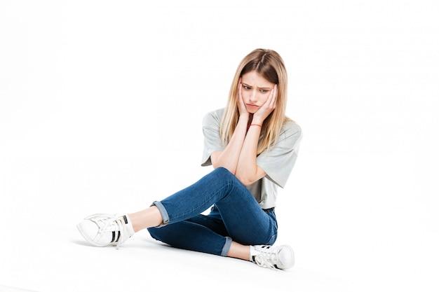 Triste mulher sentada de pernas cruzadas