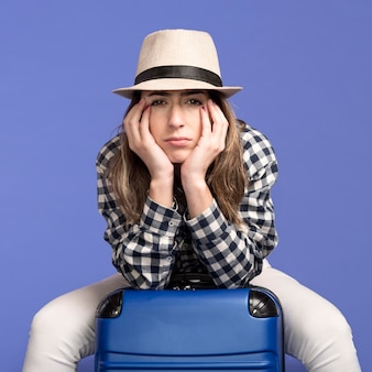 Triste mulher sentada na bagagem