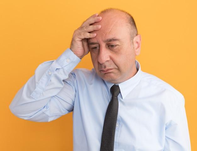 Triste olhando para o lado homem de meia-idade vestindo camiseta branca com gravata colocando a mão na cabeça isolada na parede laranja