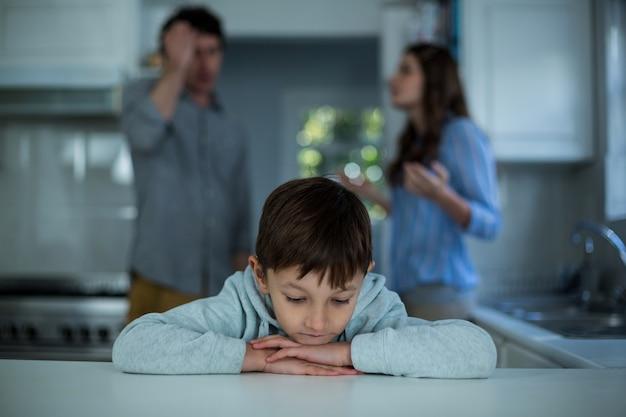 Triste rapaz sentado enquanto casal tendo argumento