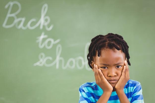 Triste rapaz sentado na sala de aula