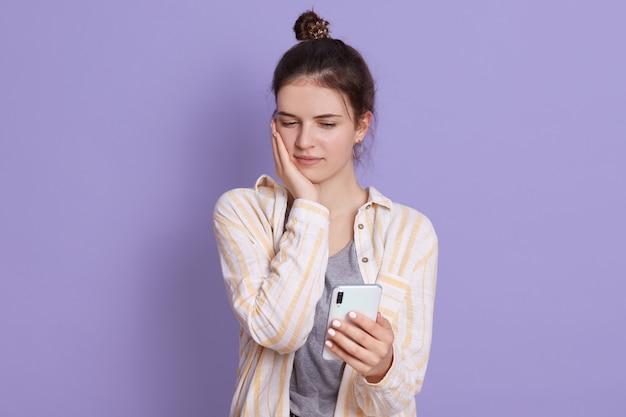 Triste senhora segurando o telefone móvel nas mãos e olhando para a tela com expressão facial triste