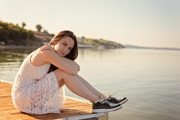 Triste solitária jovem sentado abraçando os joelhos no cais com olhos tristes, solidão, separação, apatia, depressão