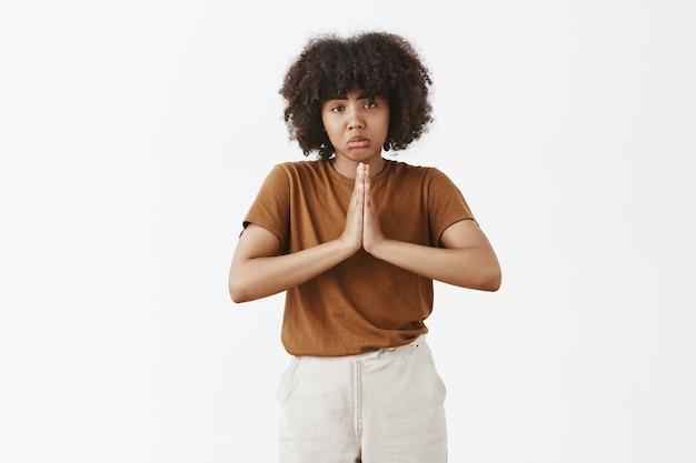 Triste triste adolescente bonita de pele escura com penteado afro franzindo os lábios em um sorriso triste franzindo a testa e segurando as mãos em oração enquanto pede ajuda ou favor sobre a parede cinza