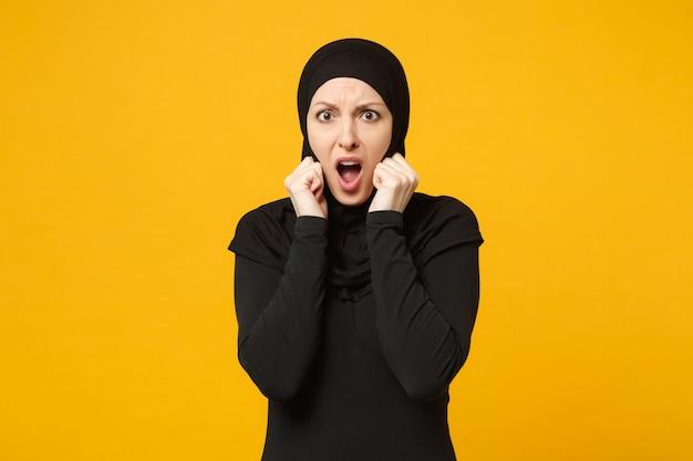 Triste triste chorar confusa jovem muçulmana árabe em roupas pretas de hijab posando isolado no retrato de parede amarela. conceito de estilo de vida do islã religioso de pessoas.