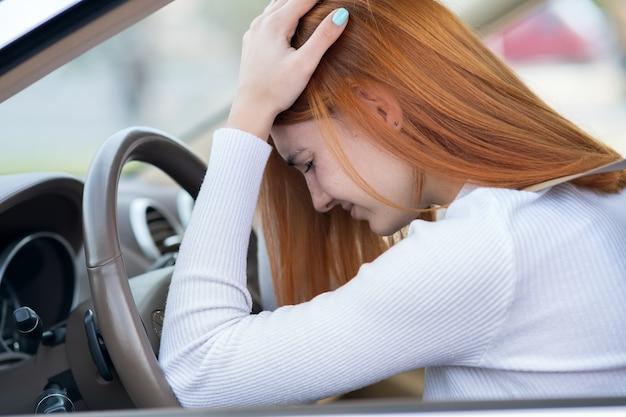 Triste yound motorista mulher sentada ao volante do carro no engarrafamento