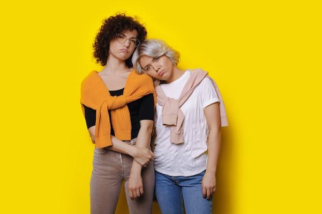 Tristes irmãs caucasianas com cabelo encaracolado posando na parede amarela de um estúdio, gesticulando com os lábios para baixo