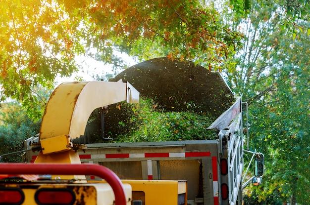 Triturador de madeira em lascas de triturador de triturador na traseira de um caminhão.