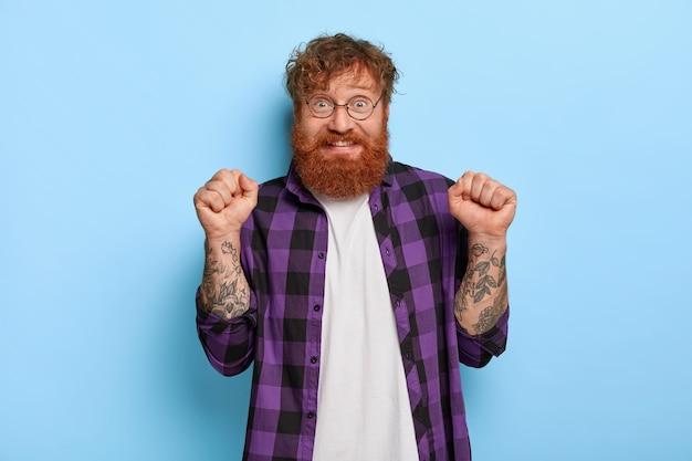 Triunfando alegre homem com cabelo vermelho, levanta os punhos cerrados, comemora vitória ou triunfo, usa óculos ópticos