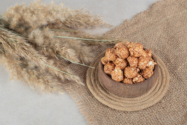 Triver debaixo de uma tigela de pipoca com sabor ao lado de hastes de erva-agulha no mármore.