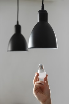 Troca da lâmpada por lâmpada led no abajur na cor preta. sobre fundo cinza claro.