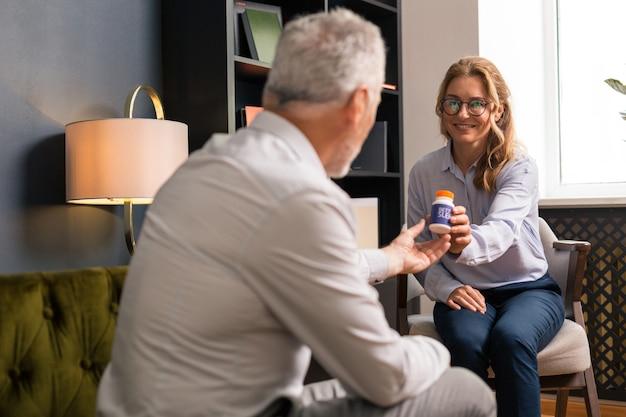 Troca de papéis. linda mulher loira de cabelos compridos sorrindo enquanto dava seus comprimidos para um psicoterapeuta sentado na frente dela