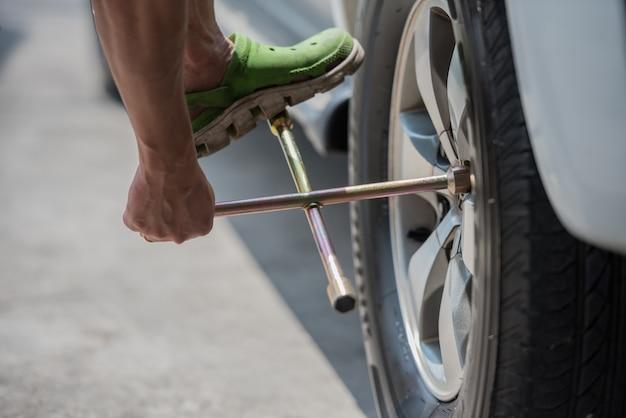 Troca de um pneu de carro, close up, fixação de carro e serviço de manutenção.
