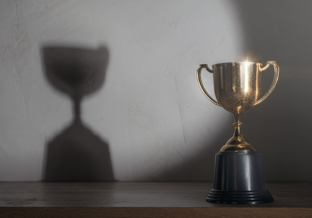 Troféu de ouro campeão colocado na mesa de madeira