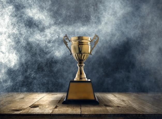 Troféu de ouro campeão colocado sobre uma mesa de madeira com fundo escuro e fumo