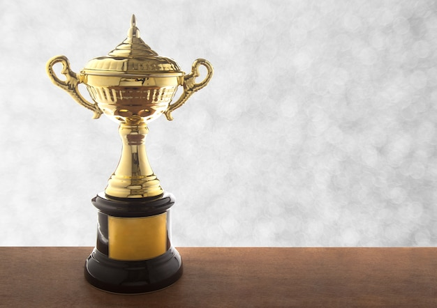 Troféu de ouro na mesa de madeira sobre fundo branco abstrato bokeh. prêmios vencedores