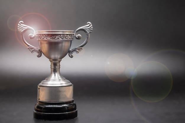 Troféu de prata em cima da velha mesa de madeira na frente do quadro-negro.